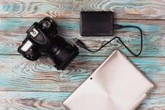 Таблетка и камера лежа на деревянной голубой предпосылке Стоковые Изображения RF