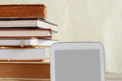 Таблетка и книги на деревянном стоковое фото