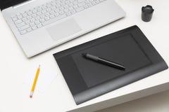 Таблетка и компьтер-книжка чертежа цифров на таблице стоковые фотографии rf