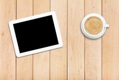 Таблетка и кофе на деревянном столе Стоковые Фото