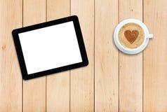 Таблетка и кофе на деревянном столе Стоковая Фотография