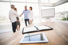 Таблетка и плановик перед бизнесменами handshaking стоковая фотография