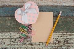 Таблетка и тетрадь подарочной коробки сердца на деревянной предпосылке Стоковые Изображения