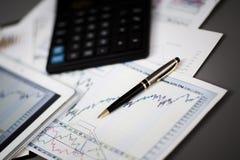 Таблетка, калькулятор, ручка и финансовые диаграммы в бизнесмене рабочего места Стоковые Фотографии RF