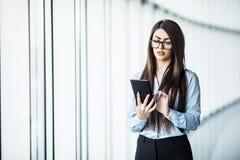 Таблетка пользы дамы дела цифровая около панорамных окон в современном офисе Стоковые Изображения RF