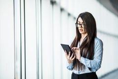 Таблетка пользы дамы дела цифровая около панорамных окон в современном офисе Стоковое Изображение RF