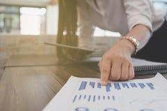 Таблетка пользы коммерсантки для того чтобы проанализировать диаграмму рынка на рабочем месте Y Стоковое Фото