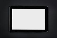 Таблетка с пустым экраном на черной таблице стоковое фото