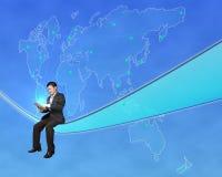Таблетка усаживания и касания бизнесмена с всемирным backgrou карты Стоковые Фотографии RF
