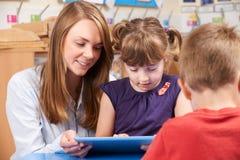 Таблетка цифров пользы зрачка начальной школы порции учителя Стоковое фото RF