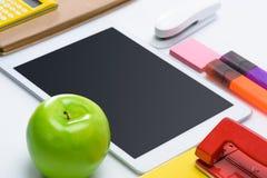 Таблетка цифров с пустым экраном и красочными школьными принадлежностями Стоковое Фото