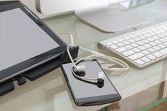 Таблетка цифров, умный телефон, место телефона уха на таблице с c Стоковые Фото
