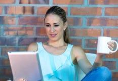 Таблетка чтения молодой женщины и выпивая кофе дома Стоковая Фотография RF