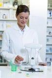 Таблетки аптекаря измеряя с масштабом фармации Стоковая Фотография RF