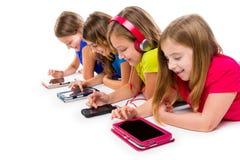 Таблетки и smatphones техника девушек ребенк сестер Стоковая Фотография