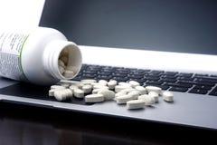 Таблетки медицины на портативном компьютере Стоковые Изображения RF