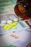 Таблетки на тайских банкнотах (бате) для концепции лекарства Стоковые Фото