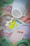 Таблетки на тайских банкнотах (бате) для концепции лекарства Стоковые Изображения
