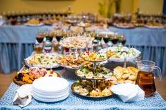Таблица банкета для банкета в ресторане таблица шведского стола, канапе, сандвичи, закуски, отрезанная таблица праздника, Стоковые Изображения