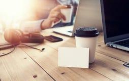 Таблица белого пустого модель-макета визитной карточки деревянная принимает отсутствующую кофейную чашку Запачканный офис тетради стоковое фото rf