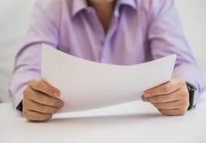 Таблица бизнесмена сидя и документ держать Стоковые Фото