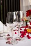 Таблица бокала установленная с украшениями лепестков розы Стоковая Фотография RF