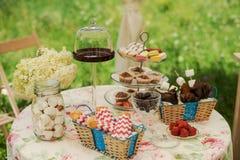Таблица десерта для партии Шоколадный торт, пирожные, сладость, macaroons, зефиры, zephyr и цветки Стоковые Изображения