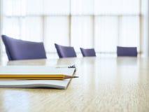 Таблица деловой встречи с местами книгой и комнатой правления карандаша Стоковые Изображения