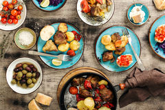 Таблица еды, зажаренное мясо с овощами, салат и закуски Стоковое фото RF