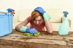 Таблица живущей комнаты женщины очищая с тканью и брызг разливают утомленное по бутылкам в стрессе Стоковое Фото