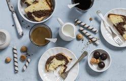 Таблица завтрака или закуски - кофе, печенья, конфета, торт, сливк на голубой предпосылке Стоковая Фотография RF