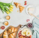Таблица завтрака с кофе, молоком, pasrties, вареньем и желтыми тюльпанами Стоковые Фотографии RF