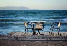 Таблица и стулья на пляже в утре раннего лета Стоковое Изображение