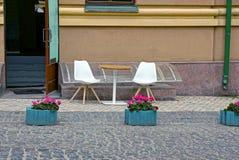 Таблица и стулья на тротуаре около дороги Стоковое Изображение RF