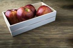 таблица коробки яблок зеленая деревянная Красные яблоки на деревянной таблице Стоковое Изображение