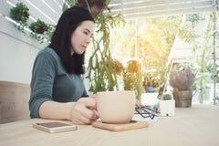 Таблица офиса при азиатская женщина наблюдая на coffe компьтер-книжки и питья Стоковые Фото