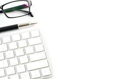 Таблица офиса с стеклом клавиатуры и ручка изолированная на белом backg стоковые фото