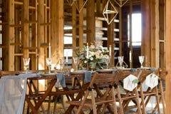 Таблица свадьбы украшения перед банкетом в деревянном амбаре Стоковое фото RF
