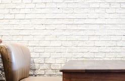 Таблица софы и древесины и белая кирпичная стена Стоковые Изображения RF