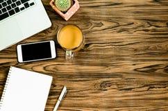 Таблица стола офиса Брайна деревянная с книгой, ручкой, кактусом и телефоном Стоковое Изображение RF