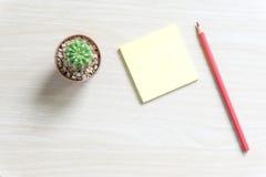 Таблица стола офиса с пробелом, бумагой, карандашем, баком завода, и поставками workplace Взгляд сверху на деревянной предпосылке Стоковое Изображение RF