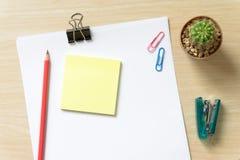 Таблица стола офиса с пробелом, бумагой, карандашем, баком завода, и поставками workplace Взгляд сверху на деревянной предпосылке Стоковое Фото