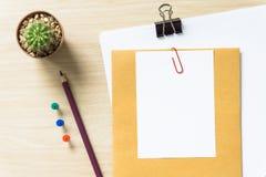 Таблица стола офиса с пробелом, бумагой, карандашем, баком завода, зажимами и поставками workplace Взгляд сверху на деревянной пр Стоковая Фотография