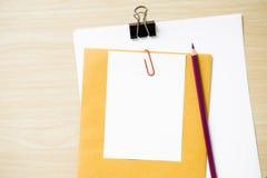 Таблица стола офиса с пробелом, бумагой, карандашем, баком завода, зажимами и поставками workplace Взгляд сверху на деревянной пр Стоковое Изображение