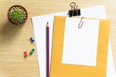 Таблица стола офиса с пробелом, бумагой, карандашем, баком завода, зажимами и поставками workplace Взгляд сверху на деревянной пр Стоковое фото RF