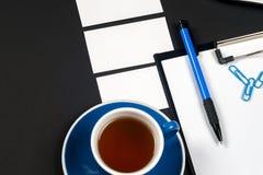 Таблица стола офиса черная с белыми компьютером, пробелом визитной карточки, цветком, кофейной чашкой и ручкой Стоковое Фото