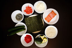 Таблица служила с ингридиентами суш и традиционной японской еды в плитах на темной предпосылке Стоковые Фотографии RF