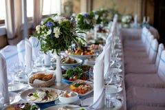 таблица служят банкетом, котор Бокалы с салфетками, стеклами и салатами Стоковая Фотография RF