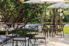 Таблицы и стулья кафа снаружи с большими белыми зонтиком и заводом Стоковое фото RF