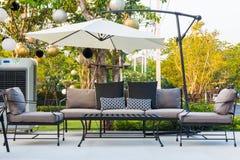 Таблицы и стулья кафа снаружи с большими белыми зонтиком и заводом Стоковые Фото